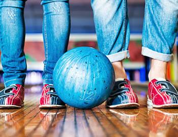 Two pairs of feet with bowling shoes on and a bowling ball