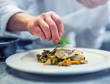 Chef putting the finishing touches on a dish at a fine dining restaurant