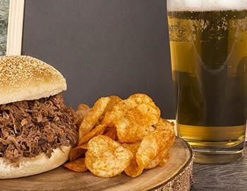 BBQ pulled pork sandwich with BBQ chips and beer