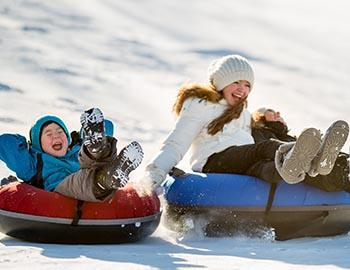 Young kid and sister bombing down the snow tube hill
