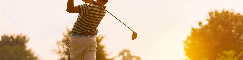Golfer swinging his club on a golf course