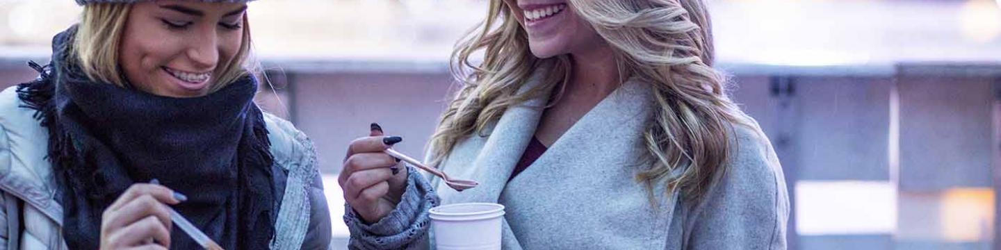 Two friends enjoying hot cocoa in Mammoth Lakes together