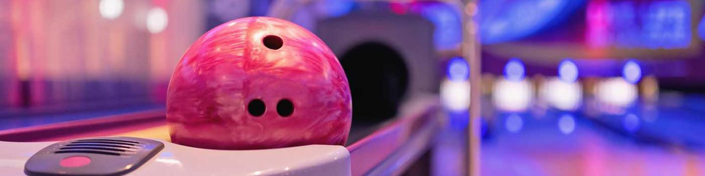 Pink bowling ball in bowling ball return at cosmic bowl in Mammoth